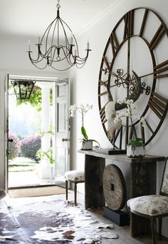 decor ideas for an entryway using a large wall clock that is metal. Decorating ideas for clocks in art gallery walls and more