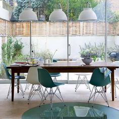 Dining area light and spacious, with large French windows leading out into the garden. The floor includes a circle of glass that is both decoration and a skylight for the basement below.