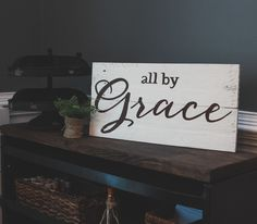 """All By Grace measures approximately 9.5""""X22"""" and is available in several wood finishes and text color choices. Please note  when making a selection, the color listed refers to wood finish. {Shown here in antique white with dark text}    OGDS pieces come ready to hang with hardware attached as wel..."""