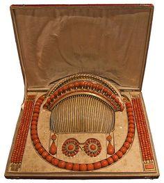 Parure en corail faceté monture or comprenant: Collier, pendant d'oreilles, paire de bracelets, boucle de cape et peignes dans son écrin d'origine en maroquin rouge doré en fer. France 1er Empire.
