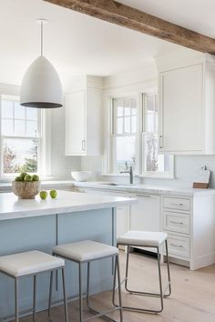 White egg shaped light pendants hang above a light blue center island topped with a honed white marble countertop seating sleek counter stools.
