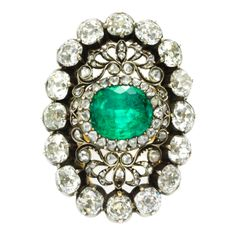 An antique emerald and diamond ring, the oval buff-top emerald with an open scroll rose-cut diamond surround and an old mine cut diamond border, mounted in silver and gold. Circa 1880