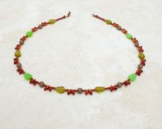 Short length boho style necklace made with silver lined amber Magatama beads, green toned leaves, chestnut brown seed beads.