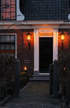 Voordeur met opstap en mooie lampen. Ook een mini levensboom.