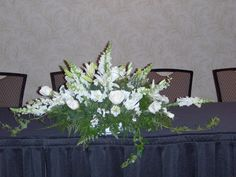 Head table arrangement with lilies,roses, lisianthus and snapdragons.