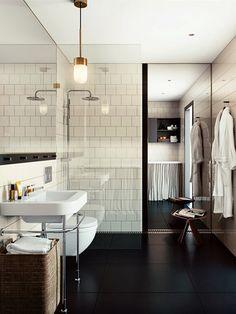 """Banheiro revestido de branco, piso preto e espelho """"embutido""""."""