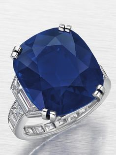 The Kelly Sapphire, a 21.71-carat Kashmir sapphire. The stone is mounted by Cartier and flanked by two trapeze-shaped diamonds.