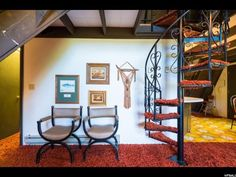 Living room with spiral staircase, matching chairs, gallery wall, and shag carpet.