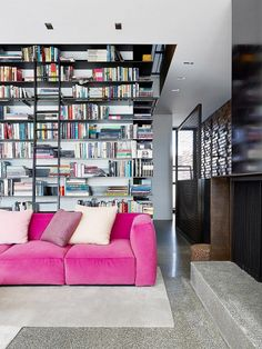 a pink sofa and a fully stacked bookshelf -- two of my most favorite design elements :)