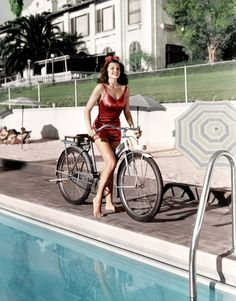 1940 Rita Hayworth on a bicycle in a swimsuit at the Beverly Hills Hotel, California. (Colorized Photo).