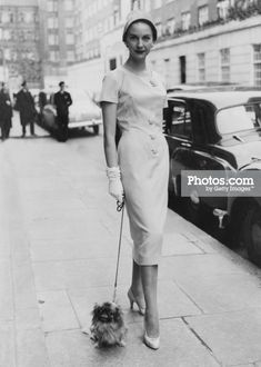 Model Shirley Worthington wearing a banana cream flannel day dress with taped and buttoned neckline, the unbelted long look is stressed with three buttons through the waist line. From the E R Hill of London Spring Collection.