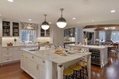 Double islands in L-shaped kitchen feature white painted fully custom Bilotta cabinets, marble tops, and brass hardware. Designed by Randy O'Kane, CKD of Bilotta Kitchens.