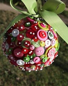 Button kissing ball/ hanging ornament - looks like a styrofoam ball form and assembled with fabric pins through the button holes.