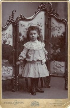Antique cabinet card, dated 18 February 1904. The subject is a very pretty little girl with dark curly hair and a lace collar dress, identified on the back as Martha Orszag (born in Vienna in 1900, so she is about 3 1/2 years old in this photo), standing in front of an elaborately decorated folding screen. The photographer is identified on the lower edge and back as Ferdinand Grega, in Vienna.