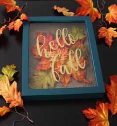 Welcome the Autumn season with this beautiful shadow box. This is made with gold glitter vinyl words on the glass, a teal colored frame, filled with autumn colored craft leaves, and a wood-themed paper background. The picture includes a teal Autumn Crafts, Holiday Crafts, Fall Halloween, Halloween Crafts, Flower Shadow Box, Autumn Decorating, Fall Projects, Dollar Tree Crafts, Hello Autumn