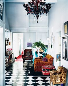 Eclectic elegance with black and white tiled floor, jewel tone furniture, and dramatic chandelier.