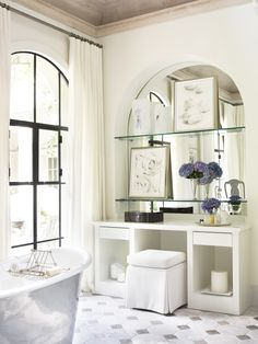 Drapery panels above an arched window, niche that mirrors the window shape along with a noteworthy tub.