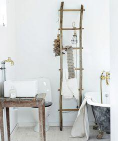 reforma baño rústico con lavabo sobre mesa madera reutilizada, bañera clásica de patas, escalera como toallero, suelo parquet.