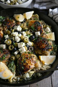 Close up image of chicken thigh cooked and covered with fresh herbs sitting in a skillet with cooked lemon rice and mixed olives and feta cheese.
