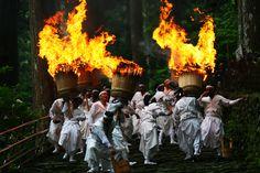 「那智の火祭り - 和歌山県熊野那智大社 - 7月」 日本三大火祭りのひとつとされ、重さ50㎏以上もある大松明の炎が参道いっぱいに乱舞します。この例大祭は、熊野那智大社から御滝前の飛滝神社への年に一度の里帰りの様子を表したものです。十二体の熊野の神々を、御滝の姿を表した高さ6mの十二体の扇神輿に移し、御本社より御滝へ渡御をなし、御滝の参道にて重さ50㎏~60㎏の十二本の大松明でお迎えし、その炎で清める神事が「那智の火祭り」です。当日は、那智大社境内にて午前11時から「大和舞」、午前11時30分から国の重要無形民俗文化財に指定された「那智田楽」が奉納されます。クライマックスとなる御滝本神事(大松明に点火)は午後2時から滝前の参道にて行われます。