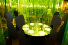 """Stephanie Goto also skipped a centerpiece, instead creating what she called a """"chan-dine-lier."""" Designed to feel like dining inside of a chandelier, the quirky table was encircled by fluorescent PVC strips. Inside, a circular bench surrounding the table was interrupted every few feet with a 2-D cut-out of a seated person."""