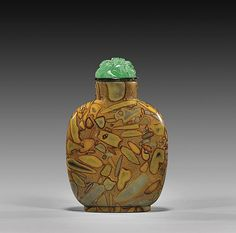 """PUDDINGSTONE AGATE SNUFF BOTTLE Attractively figured and well hollowed, puddingstone agate snuff bottle; of flattened rounded polished form; carved green glass stopper; H: 2 7/8"""""""