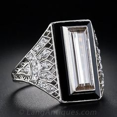 1.82 Carat Cognac Diamond Baguette and Onyx and Diamond Art Deco Ring - Truly one of the most dramatic and entrancing original Art Deco diamond rings ever. A long, slender, baguette diamond with a light cognac color weighing 1.82 carats, is displayed in a platinum bezel and a raised onyx plaque. The platinum openwork shoulders of the ring exhibit an artfully rendered diamond-set fan motif.