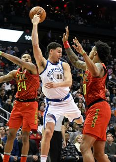 Golden State Warriors guard Klay Thompson (11) makes a backward pass as Atlanta Hawks guard Kent Bazemore (24) and forward John Collins defend during the second half of an NBA basketball game Friday, March 2, 2018, in Atlanta. (AP Photo/John Amis)