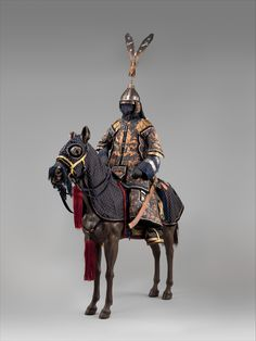 The man's armor, known as dingjia (armor with nails), is a very elaborate example of the military costume worn at the imperial court by high-ranking officials in the eighteenth and nineteenth centuries