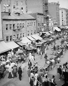 """Jewish Market on the East Side, New York between 1890 and 1901 Detroit Publishing Co. The three story building at the left of this image shows an example of the older wooden tenement houses. As described in an 1873 article in Harpers Weeky this type of wooden structure was """"liable at any time to take fire, and from its position, and from the fact that it is unprovided with fire escapes, such a casualty might involve a frightful loss of life. """""""
