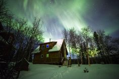 The Northern Lights stretched from horizon to horizon on Christmas morning 2013. Here they shine above a house near Healy, Alaska.