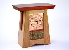 "Copper Face Mission Style Clock  $495  ""Thendara"" - This piece has two distinctive features: the copper face is hand-tooled, with raised numbers and embellishments, hand-painted black. Bisque-like custom tile with leaves and acorn, reflecting the Adirondack theme; it is painted copper and chemically aged to give it that wonderful green patina. The carcass is made of the traditional quarter-sawn white oak, and the top, tile surrounds and corbels are made of African hardwood, Paduak. 10""Hx8""Wx4""D."