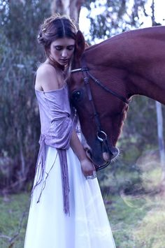 Beautiful...horse resting his head on a girls chest with a long purple dress on…