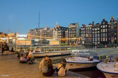 Foto de stock : People sitting and talking close to a canal with boats park in a canal at dusk. Near central Station in Amsterdam