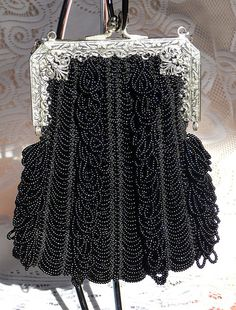 Antique filigree purse frame holding a beaded knitted purse.