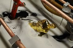 An Oscar statuette is dipped in an electrically charged tub as it is plated with gold at the R.S. Owens factory in Chicago on December 6, 2011.