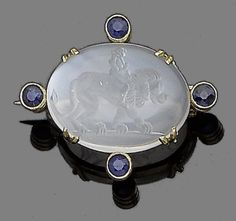 A moonstone intaglio and sapphire brooch.  The oval cabochon moonstone engraved to the reverse with a man sitting on a lion, decorated with four circular-cut sapphires, width 3.0cm