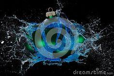A green bauble explodes, splashing blue water around