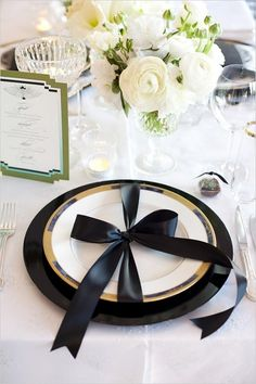 Sophisticated gold and black formal dinner table setting with an actual black tie over the plates.