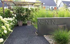 Moderne strakke tuin met hortensia's,  siergrassen en blauw split