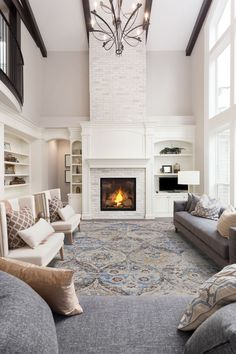 Now THIS is a grand room! This distressed piece by Dalyn is the perfect pop of color this neutral area needed. #plushrugs #distressedrugs #bluerugs #livingroom #whitefireplace #tallceilings #elegant #modern #livingroominspo #livingroomdecor