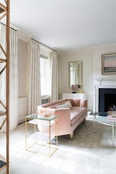Pink and gold living room features a pink curved velvet sofa lined with pink velvet lumbar pillows flanked by tiered glass and brass end tables facing an oval nickel and mirror cocktail table atop a gray rug.