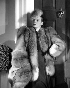"""Red fox makes a dramatic and sophisticated midwinter costume for Patricia Morison. A bulky coat with white pelts used toward the hem, a 'topknot' red fox hat and a large, luxurious muff of the same exotic fur make this one of Hollywood's most striking costumes for winter 1940."""
