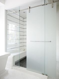 A frosted glass sliding shower door on rails opens to a walk in shower filled with black and white striped tiles lined with a white shower bench over a black shower floor.