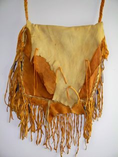 This heavily fringed buckskin bag can be used for a possibles bag or a rustic boho purse. All leather has the natural edge left and fringe has been