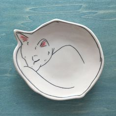 Warm Kitty Dessert Plate Slab-built porcelain plate depicting a warm sleeping kitty - curled up like they do. A personal plate for your morning scone or evening sweet treat. It makes a unique set when used as a bread plate and accompanied with the Wishing Well Dinner Plate by Early Bird Designs. Lovely alabaster color and measures approximately 6.5 inches in diameter. Handmade charm shows with this slab-built piece and a durable carved slip inlay technique creates the design. Its not merely…