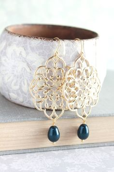 These are beautiful large gold filigree earrings. Dangling from the gold lace scalloped filigree is an deep navy blue Swarovski teardrop pearl. The pearl measures 8x11mm and compliments the lacy design perfectly. These would be lovely bridesmaids accessories or an earring you will