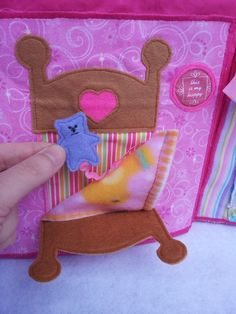 Dollhouse quiet book. Bedroom page, back of bed folds down so you can see the blanket which folds down revealing a teddy bear for the doll to cuddle. https://www.facebook.com/sparklesandstring