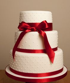 simple yet elegant white with red ribbon wedding cake. Just take off the bow!