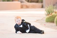 Four Seasons Scottsdale wedding, in blush and navy, with a Tara LaTour navy wedding gown with pockets. Florals are in white with beautiful succulents.  Cutest ring bearer ever!
